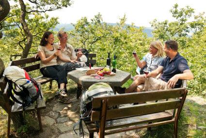 Zwei Pärchen sitzen an einem Picknick-Platz und trinken Wein im Ahrtal