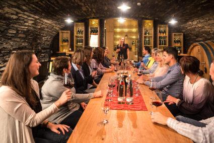 Gruppe sitzt in einem Gewölbekeller und macht eine Weinprobe im Ahrtal