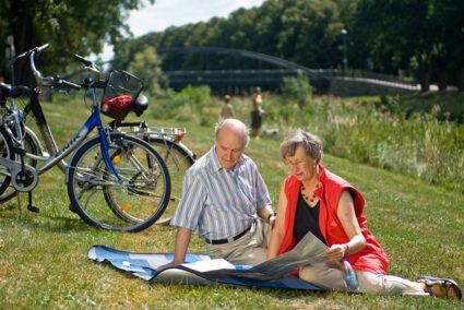 Pärchen sitz auf einer Picknickdecke und schaut in eine Fahrradkarte Ahrtal