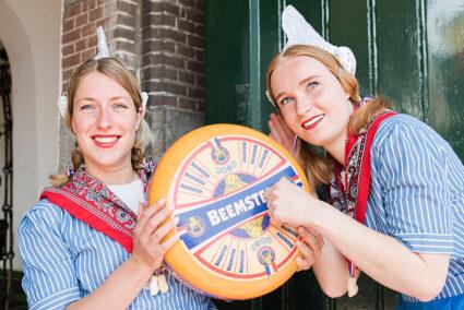 Zwei Frauen im Frau-Antje-Kostüm halten ein Rad Käse Alkmaar