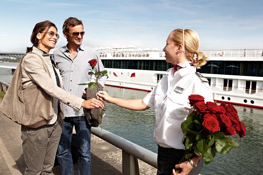 Mitarbeiter der A-Rosa übrreicht Gästen eine Rose