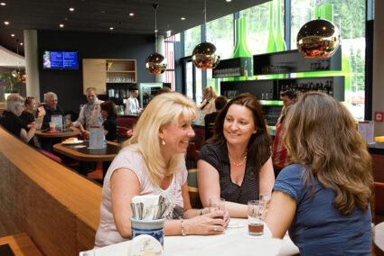 Drei Frauen sitzen in einer Bar in Attendorn und trinken Bier