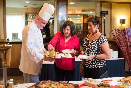 Ein Koch beident zwei Damen am Buffet in Rheinhotel Vier Jahreszeiten in Bad Breisig
