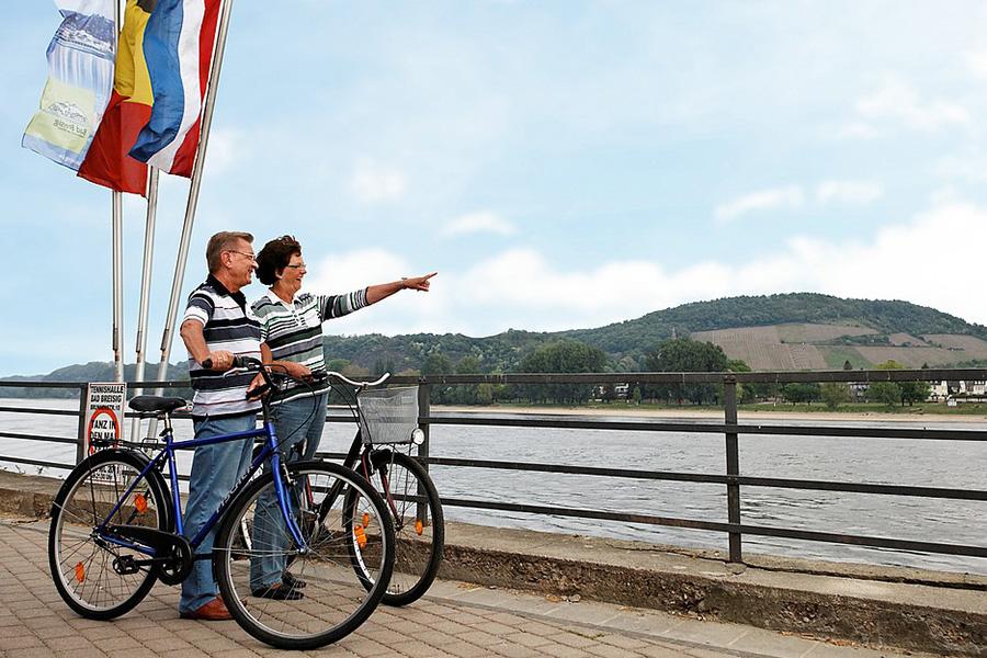 Pärchen steht mit Fahrrädern am Rhein und guckt in die Ferne