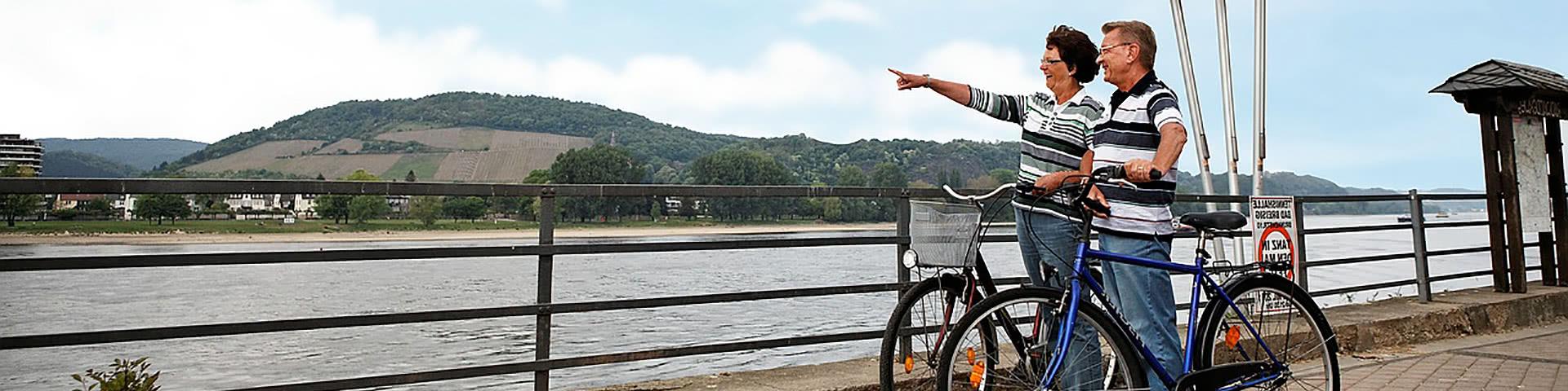Paar steht mit Fahrrädern am Rheinufer und guckt in die Ferne in Bad Breisig