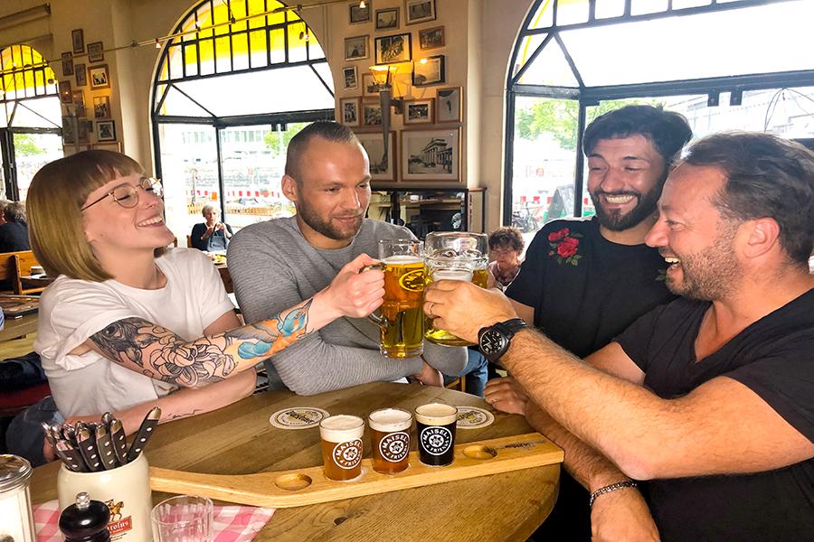 Eine Gruppe sitzt an der der Theke im Restaurant Berliner Republik und stößt mit Bier an