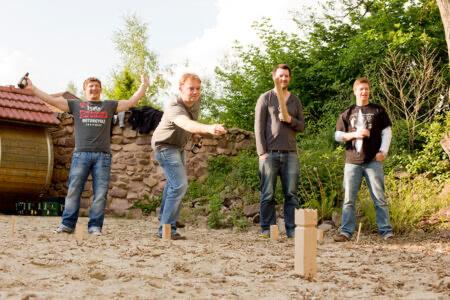 Eine Gruppe von vier Männern spielt Kubb im Beverland