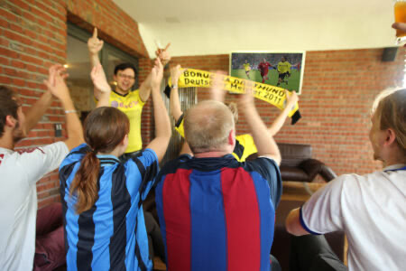 Fußballfans gucken gemeinsam Fußball und jubeln im Beverland