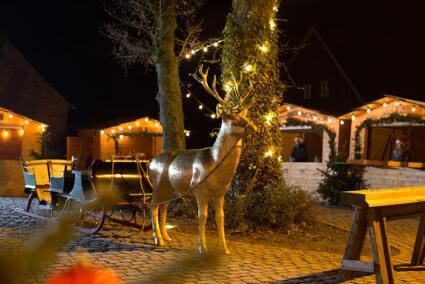 Goldener Hirsch an einen Schlitten gespannt auf dem leeren Beverland Weihnachtsmarkt