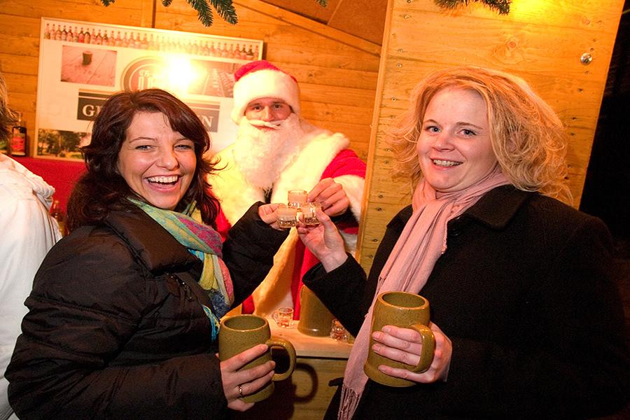 Zwei Frauen stehen an einer Weihnachtsmarkthütte und trinken einen Schnaps mit einem verkleideten Weihnachtsmarkt