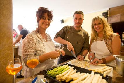 Zwei Frauen schneiden gemeinsam mit einem Koch Spargel bei einem Kochevent im Beverland
