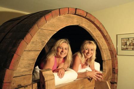 Zwei Frauen liegen in einem Bierfass-Bett im Landhotel Beverland
