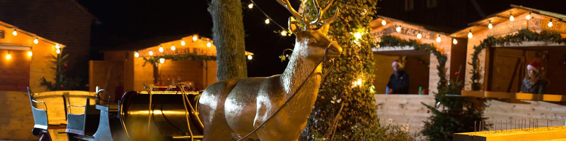 Goldener Hirsch an Schlitten gespannt auf dem Weihnachtsmarkt Beverland