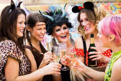 Fünf verkleidete Frauen feiern Karneval und stoßen mit einem Glas Sekt an
