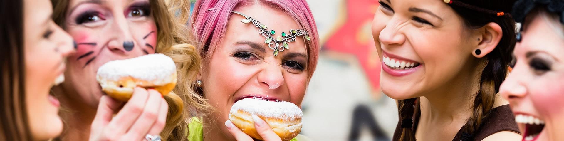 Vier verkleidete Frauen feiern Karneval und essen Berliner