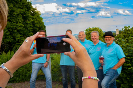 Eine Frau macht ein Gruppenfoto von einer Männergruppe in Bielefeld
