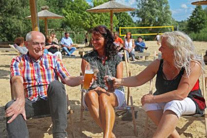 Drei Personen sitzen in Strandstühlen und stoßen mit ihren Getränken an