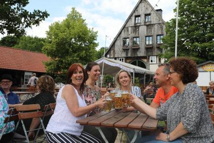 Gruppe sitzt im Biergarten am Seekrug und stößt mit einem Bier an