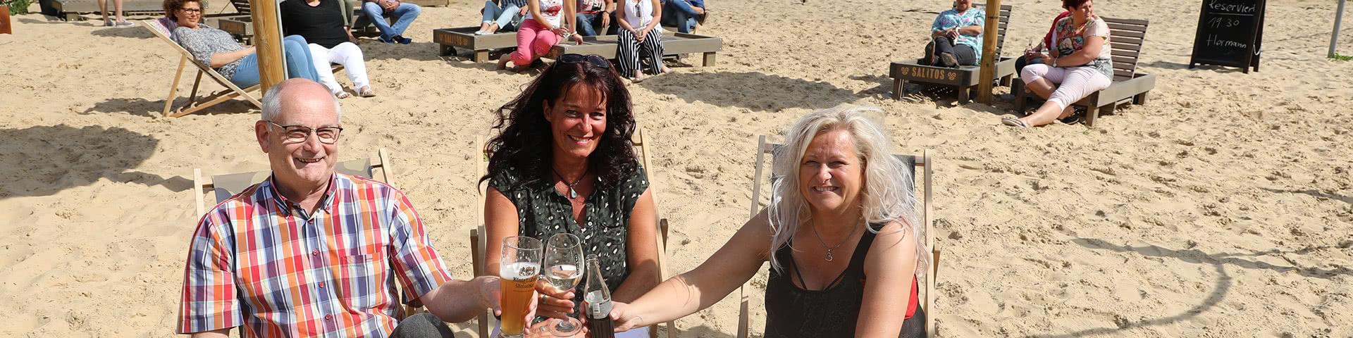 Gruppe sitzt Am Obersee Beach in Bielfeld und stößt mit Getränken an