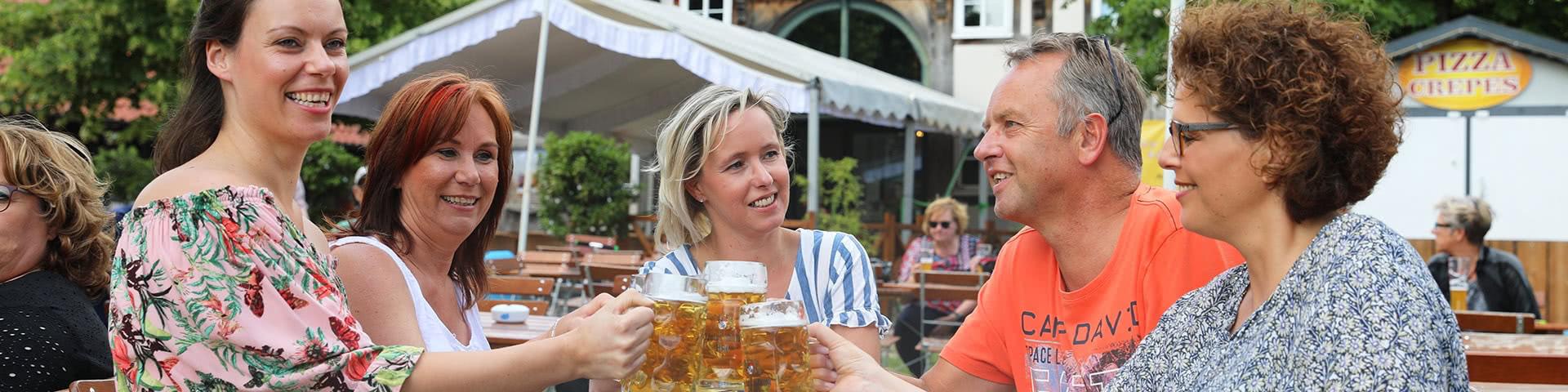 Gruuupe stößt mit einem Glas Bier im Biergarten in Bielefeld an