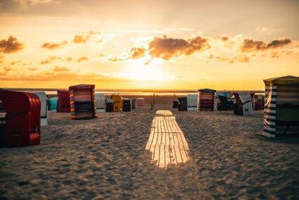 Der Strand von Borkum mit vielen bunten Strandkörben bei Sonnenuntergang