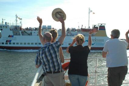 Menschen am Hafen in Borkum winken einer ankommenden Fähre