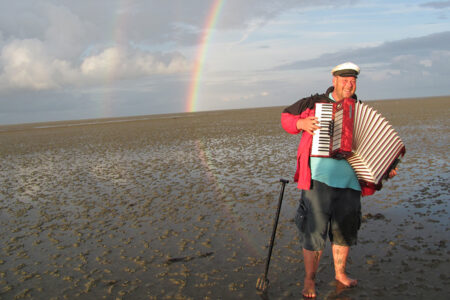 Albertus Akkermann steht im Watt und spielt Akkordeon