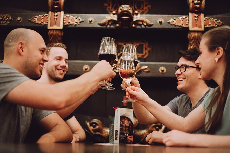Eine Gruppe stößt mit einem Glas Wein an im Ratskeller in Bremen