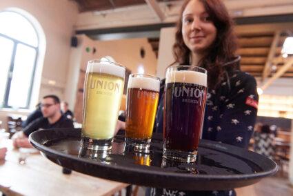 Eine Kellnerin mit einem Tablett mit drei verschiedenen Bieren in der Union Brauerei in Bremen