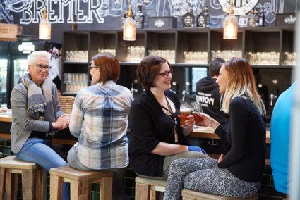 Menschen sitzen an einer Theke in der Union Brauerei in Bremen