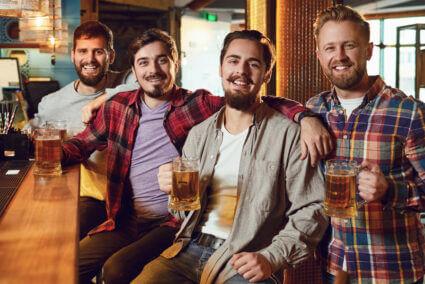 Vier Männer sitzen zusammen an einer Theke in einer Kneipe in Bremen und trinken Bier