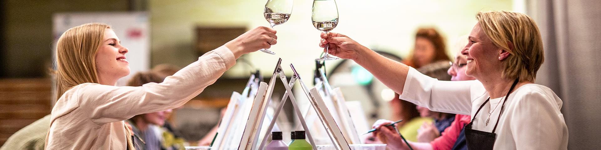 Zwei Frauen prosten sich mit einem Glas Wein zu bei einer Artnight in Bremen