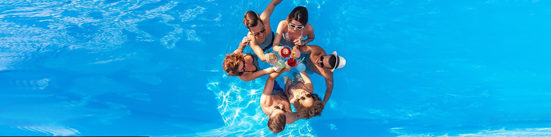 Gruppe steht in einem Kreis in einem Pool und stößt mit Cocktails an in Bulgarien