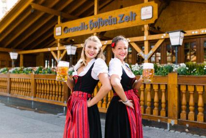 Zwei Frauen in Dirndl und mit einem Maß Bier in der Hand stehen vor dem Hofbräuzelt auf den Cannstatter Wasen