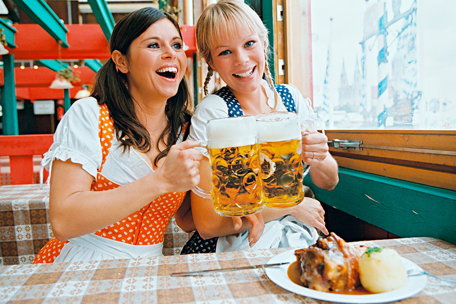 Zwei Frauen in Dirndl trinken gemeinsam Bier und essen Haxe mit Knödeln