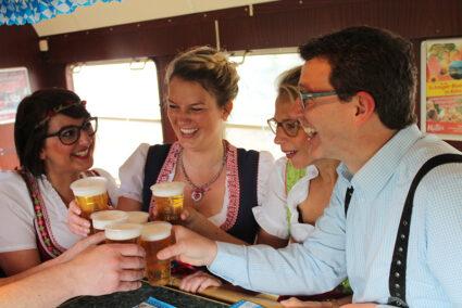 Gruppe in Tracht stößt mit Bier an im Partyzug auf dem Weg nach Cannstatt
