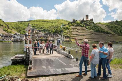Zwei Gruppen verabschieden sich an einem Schiffsableger an der Mosel in Cochem