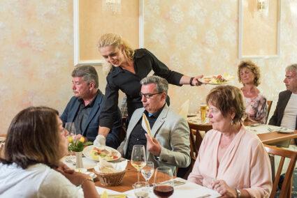 Kellnernin serviert Gruppen Essen in einem Restaurant in Cochem