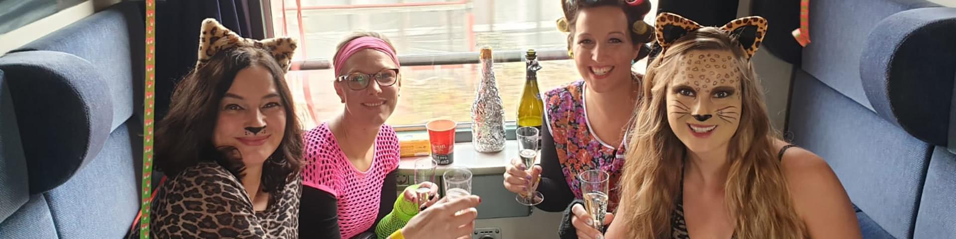 Verkleidete Frauengruppe trinkt gemeinsam Sekt im Partyzug auf dem Weg nach Cochem