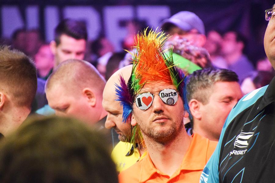 Mann mit einer bunten Perücke auf einem Dart-Turnier