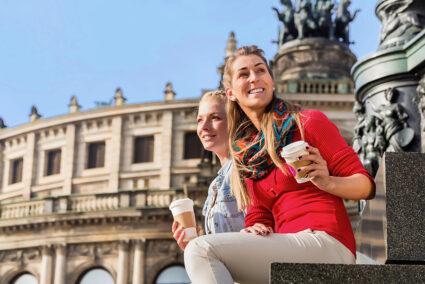 Zwei Touristinnen sitzen vor der Semper Omper und trinken einen Kaffee