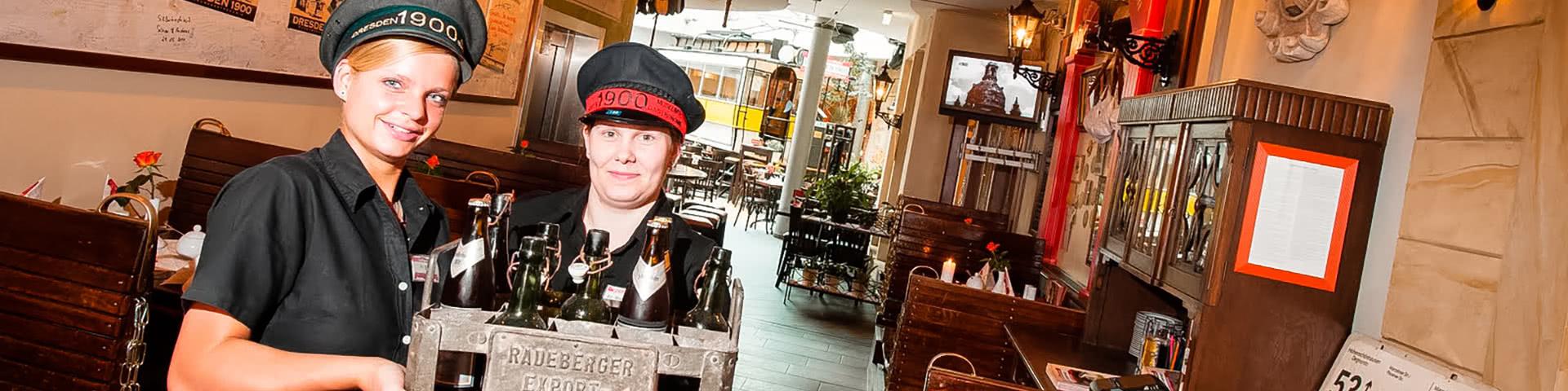 Zwei Kellnerinnen mit einer Box Bier in einem Restaurant in Dresden