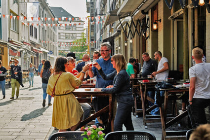 Gruppe stößt geminsam mit einem Altbier an in der Altstadt von Düsseldorf