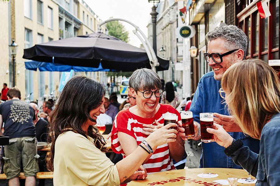 Fröhliche Gruppe trinkt gemeinsam Altbiier in der Altstadt von Düsseldorf