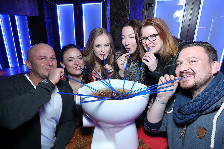 Gruppe trinkt mit Stohhalmen aus einer Toilette im Oberbayern in Düsseldorf