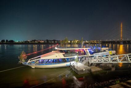 Das Eventschiff KD-Rheinkrone an einem Anleger in Düsseldorf bei Dunkelheit