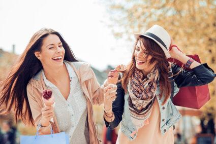 Zwei Freundinnen essen auf gemeinsamer Shopping-Tour durch Düsseldorf ein Eis