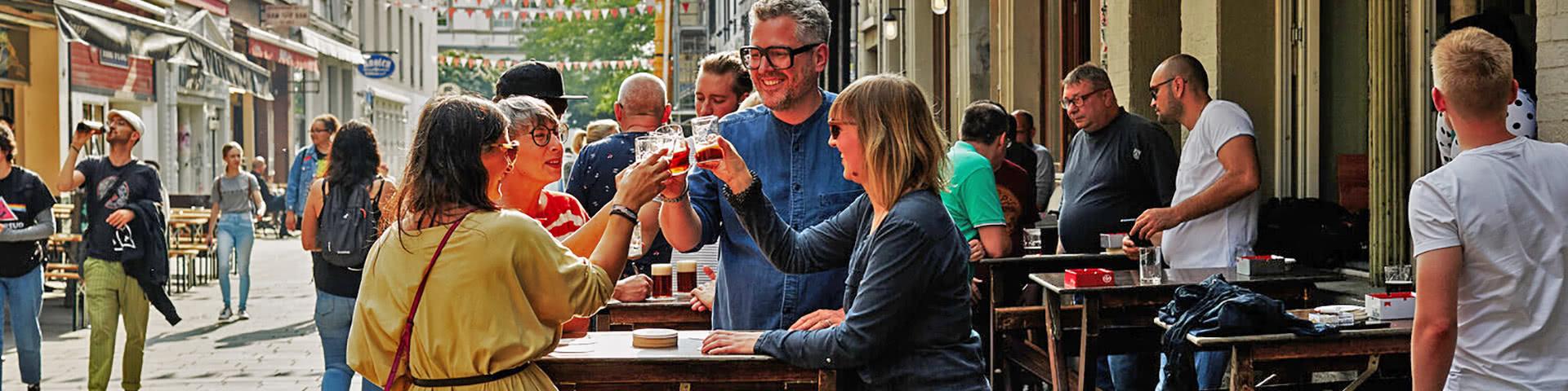 Gruppe stößt mit Altbier in der Düsseldorfer Altstadt an