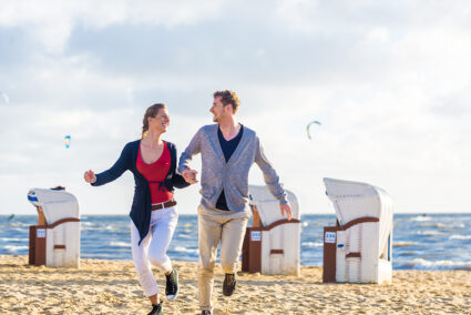 Glückliches Pärchen läuft am Strand von Egmond ann Zee entlang