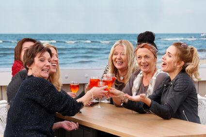 Sechs Frauen sitzen auf einer Terasse mit Meerblick in Egmond aan Zee und trinken gemeinsam Aperol Spritz